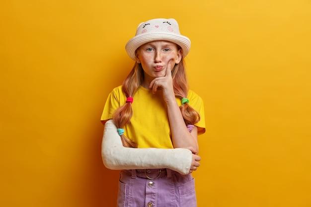 La imagen de una niña pensativa mantiene el dedo en la mejilla y piensa profundamente, ha hecho una mueca de disgusto, contempla cómo recuperarse rápidamente, se ha roto el brazo mientras jugaba en el patio de recreo y se cayó del columpio