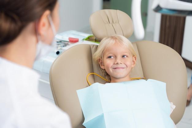 Una imagen de una niña pequeña que hace que un médico revise sus dientes