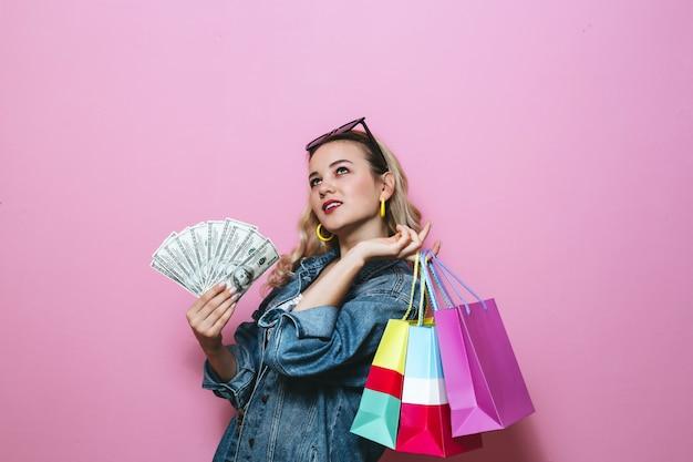 Imagen de una niña rubia feliz pensando en algo y sosteniendo billetes y bolsas de compras en la pared rosa