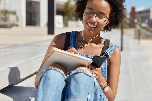 Imagen de niña satisfecha con piel negra, hace lista de verificación de planes en el diario, escucha música en la lista de reproducción a través del teléfono celular, sonríe, disfruta de un día soleado en la calle, posa en las escaleras de la ciudad. el autor escribe ideas