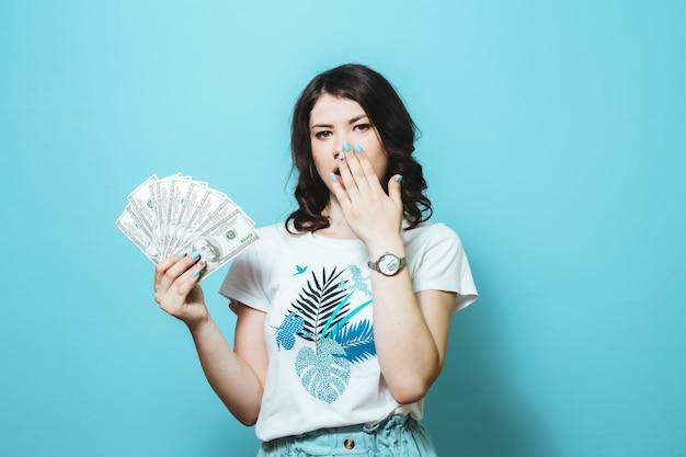 Imagen de una niña sorprendida sosteniendo un montón de billetes y mostrar gestos aislados sobre la pared azul
