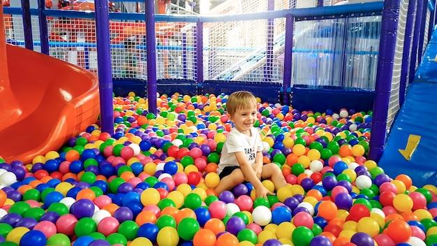 Imagen de un niño de 3 años jugando y divirtiéndose en el patio de recreo con un montón de pequeñas bolas de plastc de colores. niño disfrutando del parque de atracciones en el centro comercial.