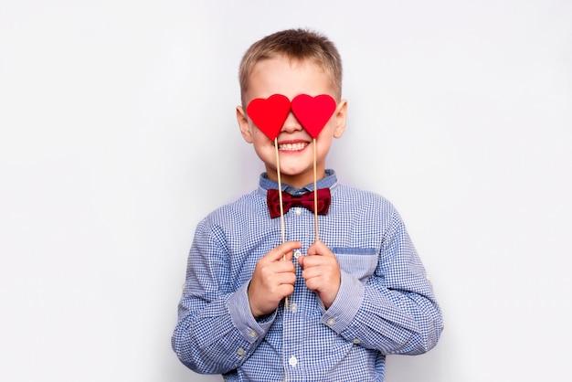 Imagen de un niño feliz y enamorado con dos corazones rojos
