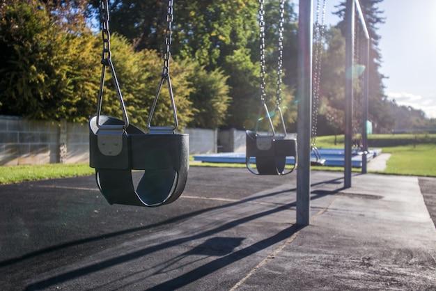 Imagen de los niños swing establecido en el parque verde.