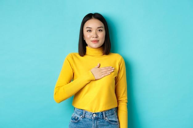 Imagen de la orgullosa mujer asiática sonriente sosteniendo la mano en el corazón, mostrando respeto al himno nacional, de pie sobre fondo azul.