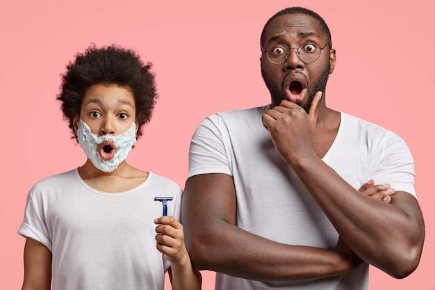 Imagen de un padre asombrado de piel oscura que mantiene la mano debajo de la barbilla y le da lecciones de cómo afeitarse a su pequeño hijo adolescente