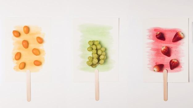Imagen de paletas en palo sobre salpicaduras de acuarela