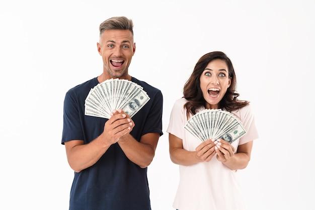 Imagen de una pareja amorosa adulta gritando sorprendida aislada sobre la pared blanca con dinero.