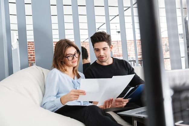 Imagen de una pareja amorosa joven concentrada en casa en el interior usando la computadora portátil trabajar con documentos.