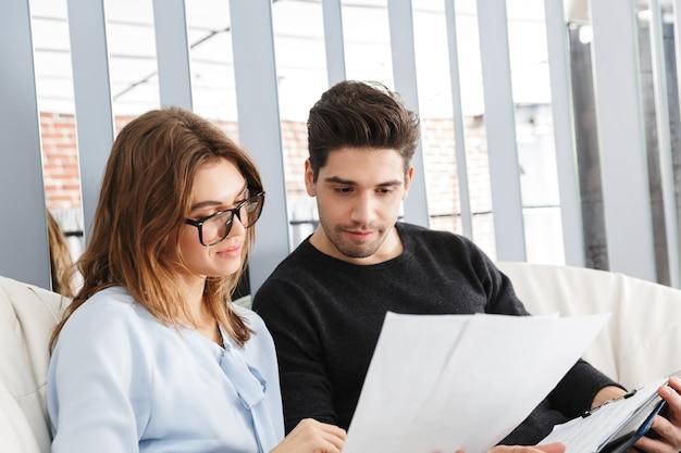 Imagen de una pareja amorosa joven seria en casa en el interior trabaja con documentos.
