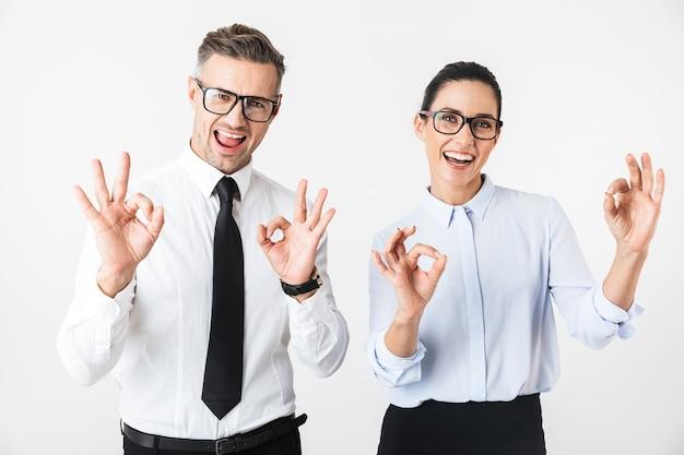 Imagen de la pareja de jóvenes colegas de negocios feliz aislado sobre una pared blanca que muestra un gesto bien.