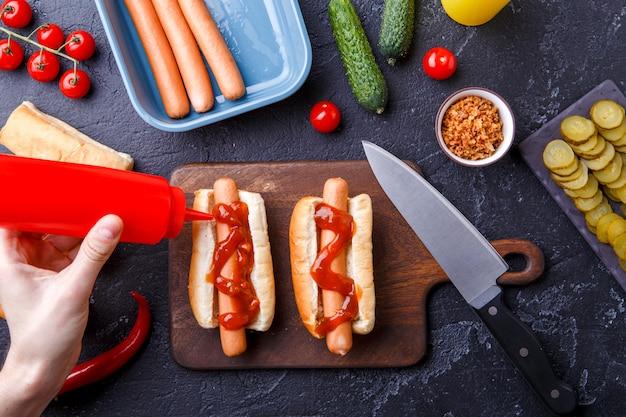 Imagen en la parte superior de la mesa con ingredientes para hot dogs, tabla de cortar, manos de hombre