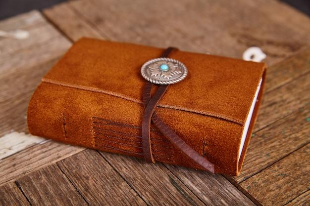 Imagen de pequeño diario cerrado de cuero con concho e hilo sobre tableros de madera