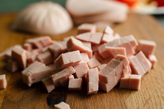 Imagen de un pequeño montón de salchichas en rodajas para cocinar en una mesa de madera en la cocina
