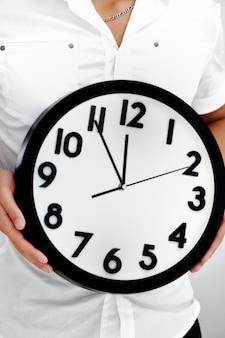 Imagen de una persona que sostiene un reloj en sus manos