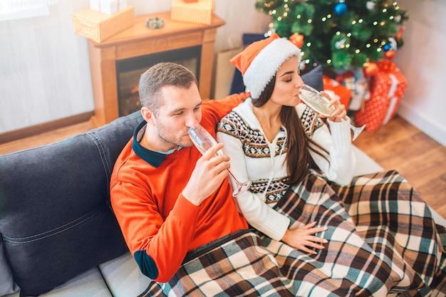 Imagen de personas sentadas en el sofá y bebiendo champaña de gafas. son relajados y tranquilos.