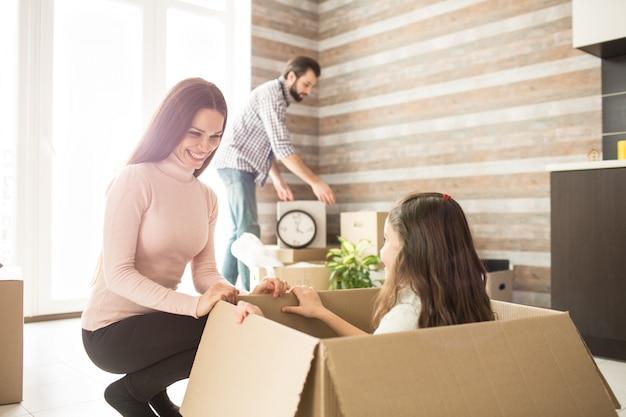 Imagen de personas trabajadoras. el hombre está poniendo una caja de sartenes sobre la pequeña mesa. su esposa está sentada de rodillas cerca de su hija y la mira con una sonrisa. pequeña niña está mirando a su madre.