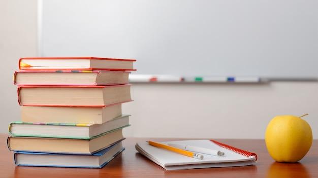 Imagen de pila de libros sobre la mesa contra la pizarra