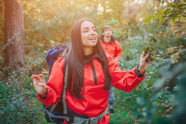 Imagen positiva de joven disfrutando. ella mantiene los ojos cerrados y sonríe. guy camina detrás de ella. ellos viajan. la gente está en el bosque.