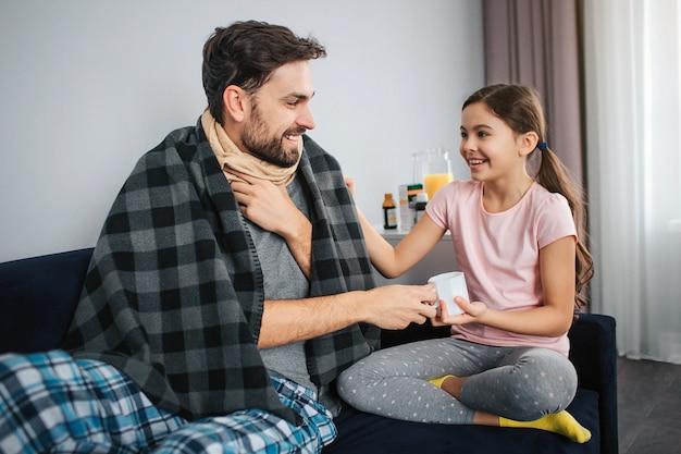 Imagen positiva del joven sentado junto a su hija. sonríen a cada uno. guy está enfermo sostienen la taza blanca juntas.