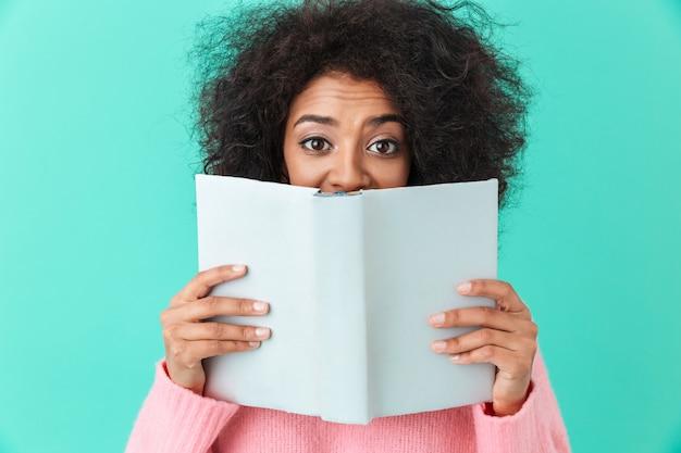 Imagen positiva de la mujer estadounidense de 20 años con peinado afro y cubriéndose la cara con un libro interesante, aislado sobre la pared azul