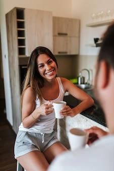 Imagen del primer del café de consumición de la mañana de los pares felices en la cocina.
