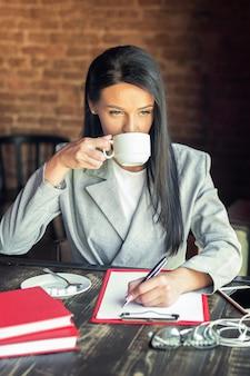 La imagen del primer de una empresaria está escribiendo en el blanco en blanco mientras que bebe el café en el café.