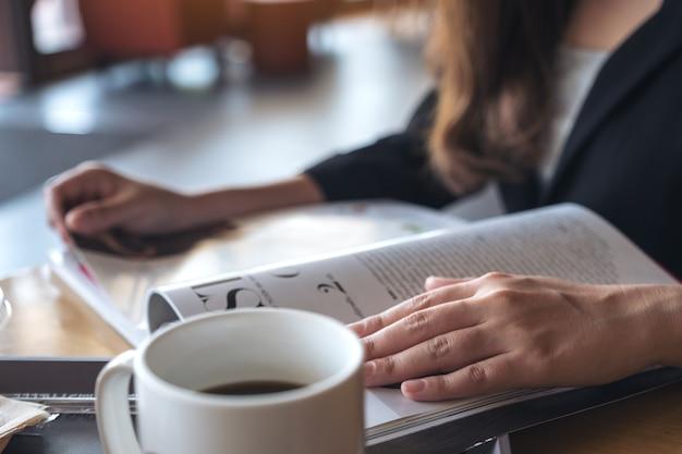 Imagen del primer de una empresaria que lee un libro con la taza de café en la tabla en café