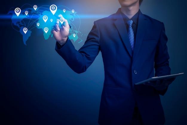 Imagen del primer del hombre de negocios que asigna la posición global con la tableta