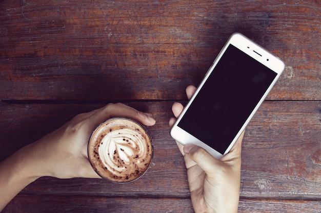 Imagen del primer de las manos de la mujer que usa smartphone en el café mientras que bebe el café.