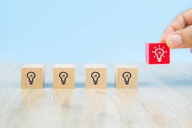 Imagen de primer plano de bloques de juguete de madera en forma de cubo recogidos a mano con símbolo de bombilla, ideas apiladas para la creatividad y la innovación.