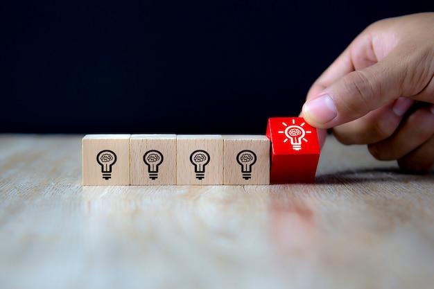 Imagen de primer plano de bloques de juguete de madera en forma de cubo recogidos a mano con símbolo de bombilla.