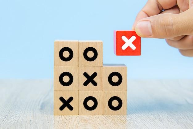 Imagen de primer plano de bloques de juguete de madera en forma de cubo recogidos a mano con el símbolo x.