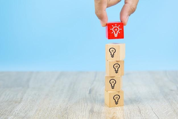 Imagen de primer plano de bloques de juguete de madera recogidos a mano con forma de cubo con símbolo de bombilla apilados.