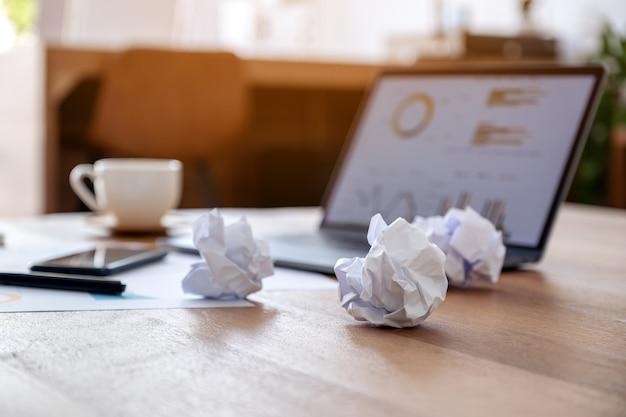 Imagen de primer plano de una computadora portátil, teléfono móvil y papeles arruinados sobre la mesa de madera en la oficina