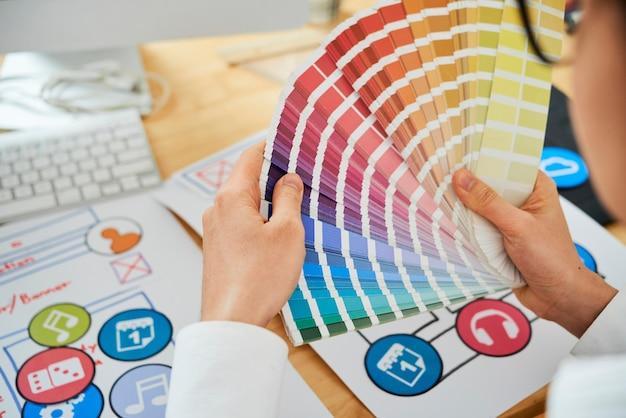 Imagen de primer plano del diseñador gráfico que trabaja con la paleta de colores y elige el tono perfecto para la pantalla de color ...