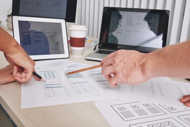 Imagen de primer plano de diseñadores de ui y ux señalando diseños de interfaz de aplicaciones móviles