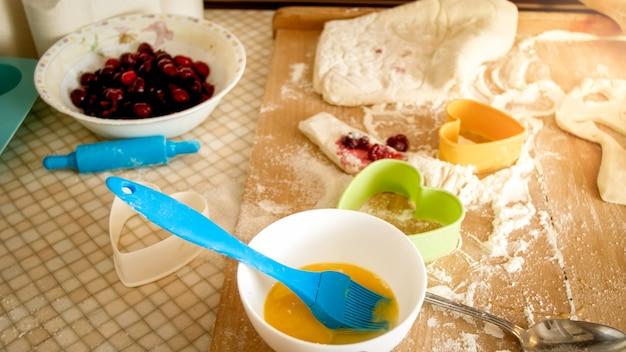 Imagen de primer plano de una gran cantidad de ingredientes y utensilios de cocina para cocinar y panadería en un mostrador de madera