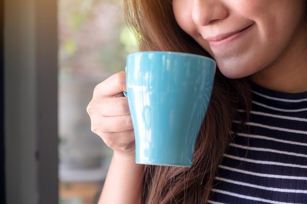 Imagen de primer plano de una hermosa mujer asiática que huele y bebe café caliente
