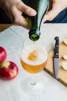 Imagen de primer plano del hombre vertiendo cidre premium en vidrio. vista superior de manos masculinas vertiendo vino de manzana vintage en hermoso vaso en mesa rústica