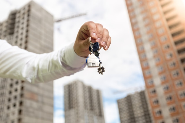 Imagen de primer plano del joven empresario sosteniendo llaves de nuevas propiedades inmobiliarias