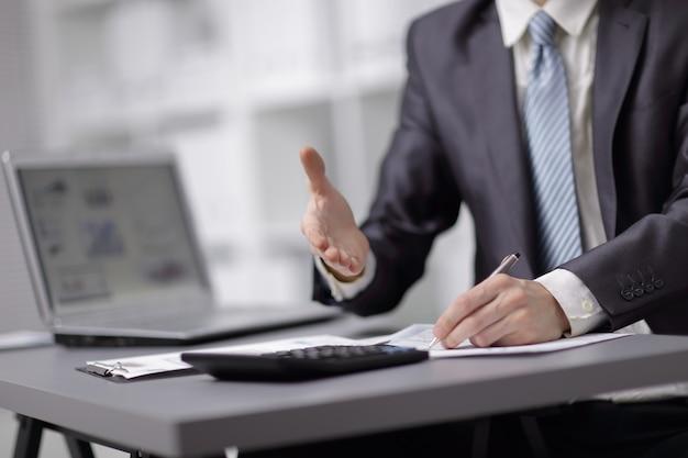 Imagen de primer plano de la mano de un hombre de negocios con un traje oscuro saludando a alguien.