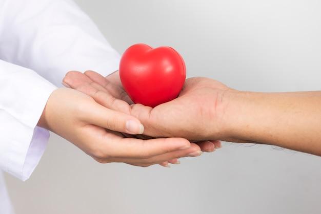 Imagen de primer plano de la mano de un médico tomados de las manos con un corazón en las manos