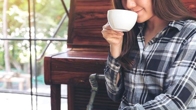 Imagen de primer plano de una mujer asiática sosteniendo una taza de café antes de beber