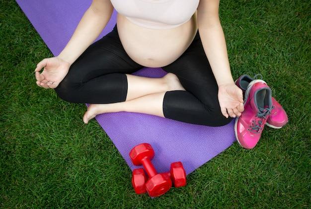 Imagen de primer plano de la mujer embarazada meditando sobre la estera de fitness al aire libre