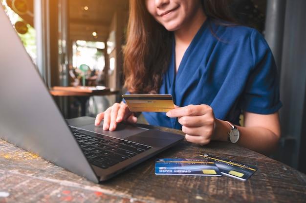 Imagen de primer plano de una mujer de negocios con tarjetas de crédito mientras usa la computadora portátil