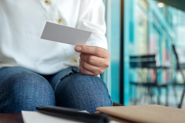 Imagen de primer plano de una mujer sosteniendo una tarjeta de presentación vacía en blanco