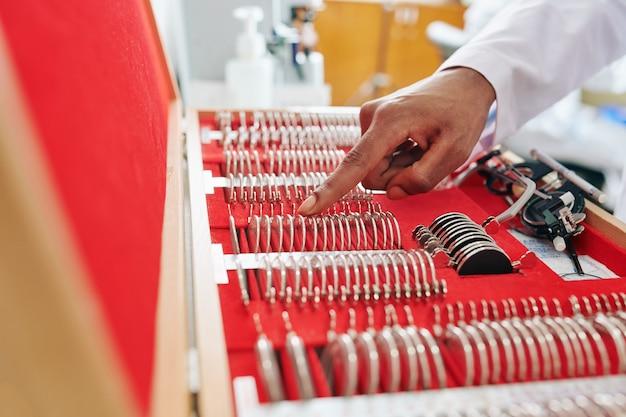 Imagen de primer plano del oftalmólogo eligiendo los lentes correctos del gran conjunto para marcos de prueba