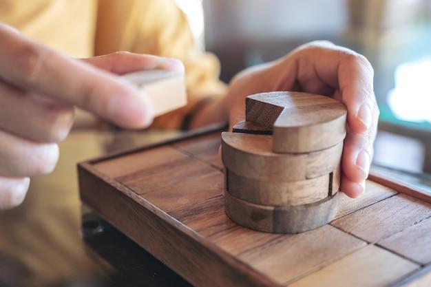 Imagen de primer plano de personas jugando y construyendo juego de rompecabezas de madera redonda