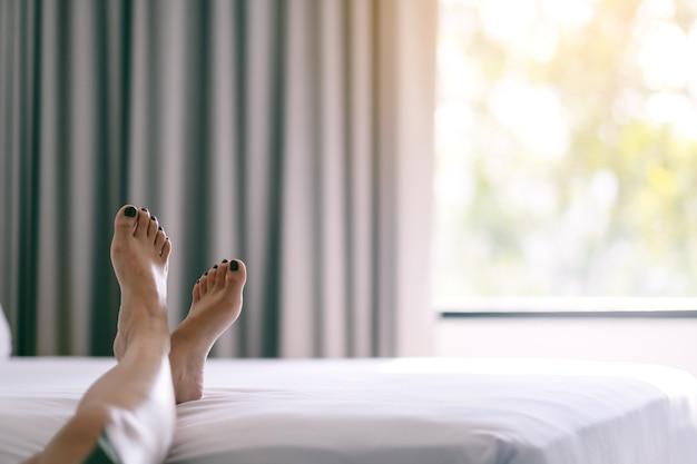 Imagen de primer plano de los pies de una mujer en una cama blanca